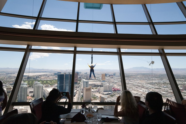 Diners in the Top of the World restaurant at the Strat or Stratosphere Hotel Tower & casino, watch a skyjump  while eating, Las Vegas USA