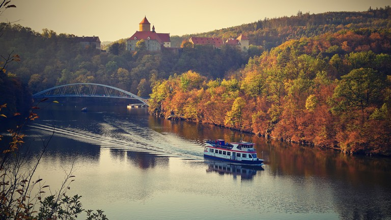 Castle Veveri - City of Brno, Czech Republic - Europe. Beautiful autumn landscape with castle. Brno dam with boat and sunset at the golden hour. Autum