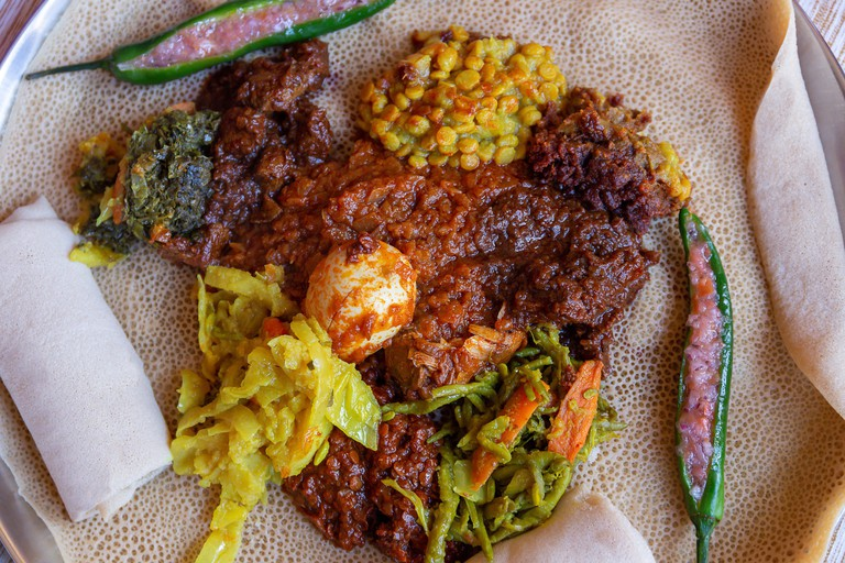 Injera served with Chicken and egg Doro Wat, berbere, vegetables and lentils. Injera, the national dish of Ethiopia, is a sourdough flatbread made