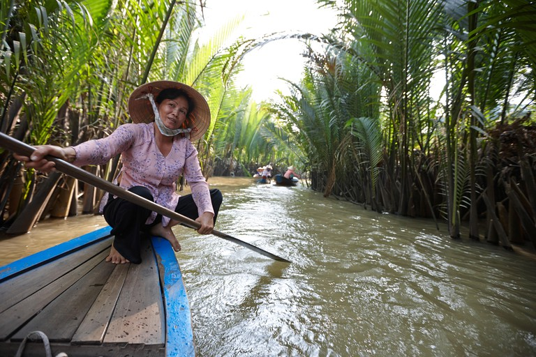 Woman canoeing tourists boats, Thoi Son island tour, My Tho, Tien Giang Province, Vietnam