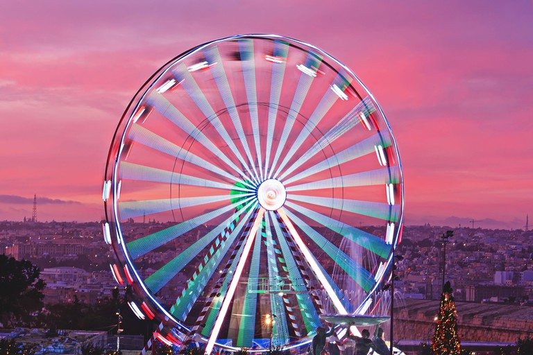 Closeup colorful Ferris wheel against sunset pink sky and Malta cityscape. Christmas market in Valletta Malta aerial view, motion blur, selective focus