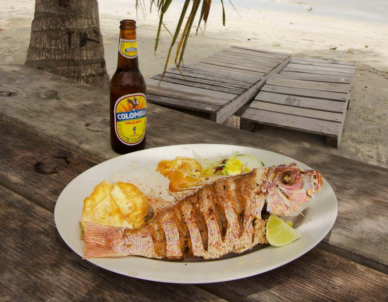 WE8DP6 Colombia, Providencia Island, Suroeste beach restaurant facing the Caribbean Sea, plate of grilled fish accompanied by a Colombia beer