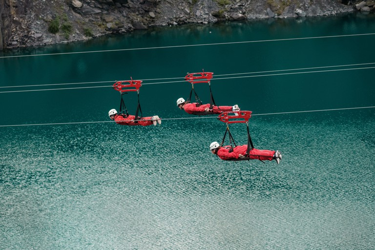 Three people on the Velocirty 2 zip lines at Zip World Penrhyn Quarry, North Wales, UK 2AHTMAW