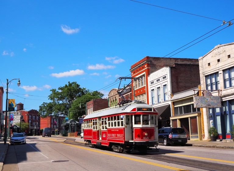 MEMPHIS, TENNESSEE - JULY 23, 2019: An electric streetcar trolley cruises along under it's power lines on Main St. in Memphis, Tennessee on a summer d