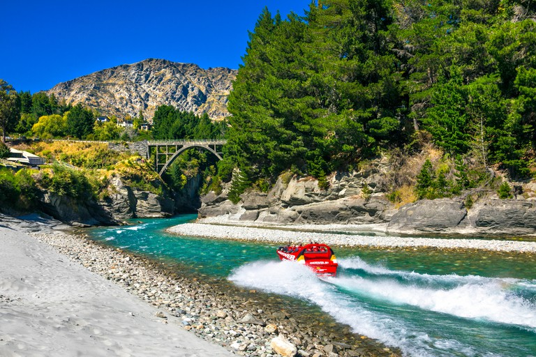 Red rib boat speeding down a river, Shotover Jet Rib Boat experience near Queenstown, New Zealand