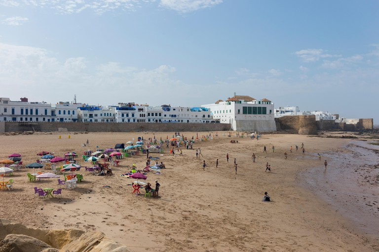 Asilah, Morocco-September 10, 2019: People on a beach in front of the fortified town of Asilah on the northwest tip of the Atlantic coast of Morocco