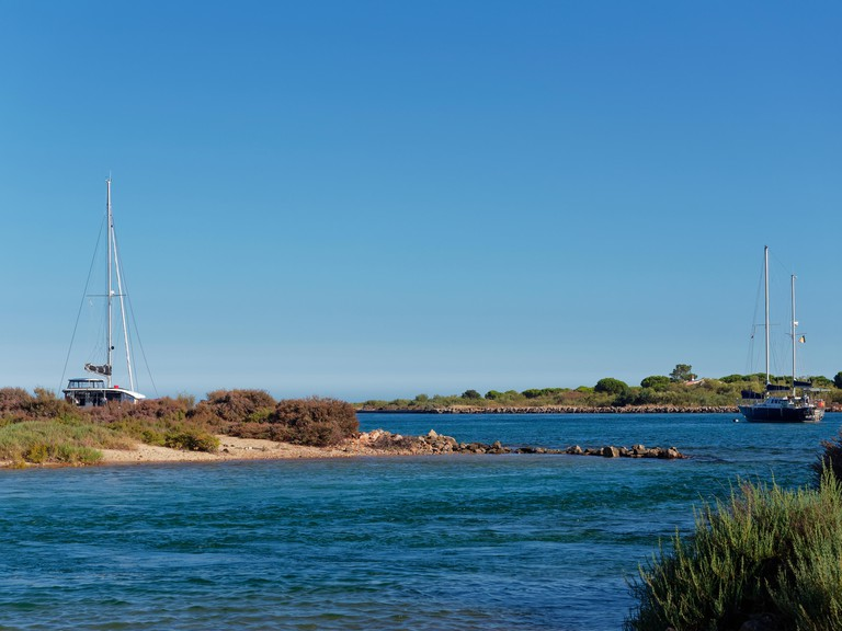 Yachts moored between the Islands of Ilha Da Culatra off the Portuguese Algarve Coast on a sunny, hot July afternoon.