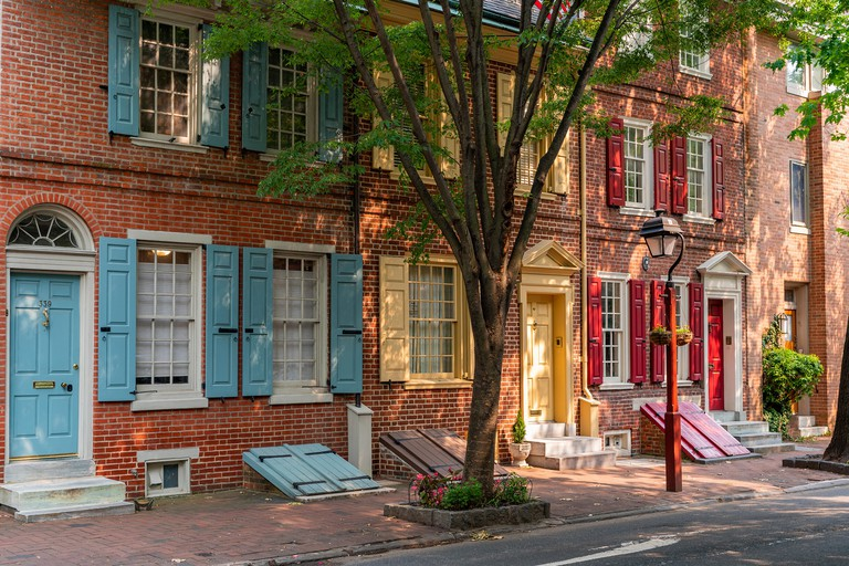 Afternoon sunshine lights up colourful wooden shutters on historic row houses in South 4th Street, Society Hill.
