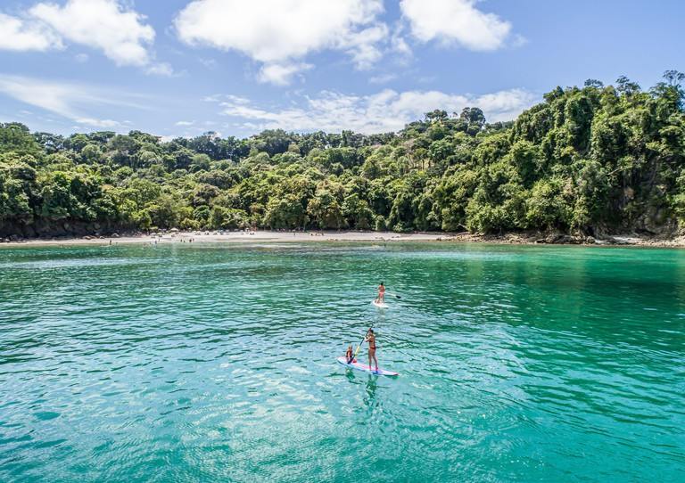 Manuel Antonio Costa Rica 02.11.2019 SUP Stand up Paddle boarding in blue bay with empty beach Central America.