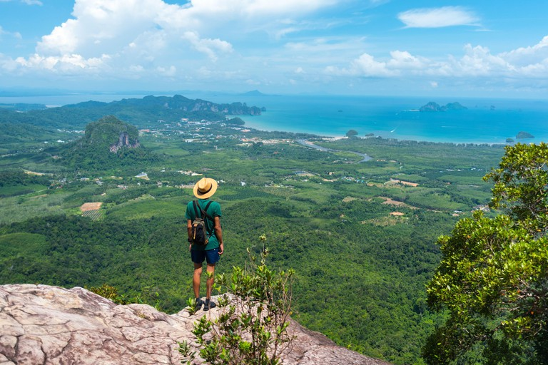 Traveler in hat stands on rock high in mountains landscape & sea on horizon. View of Ao Nang bay and islands from Dragon Crest at Khao Ngon Nak Trail