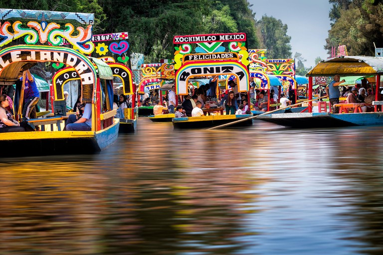 Blurred water at colorful Xochimilco on a Saturday afternoon, Mexico City, Mexico.