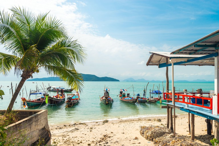 Koh Samui, Thailand - January 2, 2020: Authentic Thai fishing boats docked at Thong Krut beach in Taling Ngam on a day