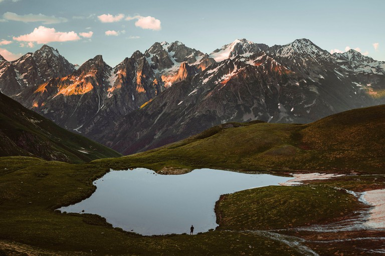 Hikers at Koruldi Lakes look out on the mountains of the Great Caucasus in the evening light, Upper Svanetia, Georgia