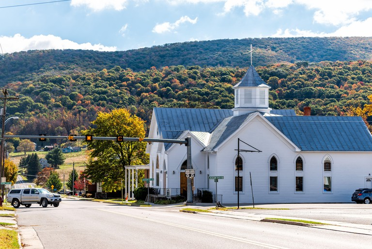Monterey, USA - October 18, 2019: View of main street road and autumn mountain trees with old architecture church building in appalachia in Highland C