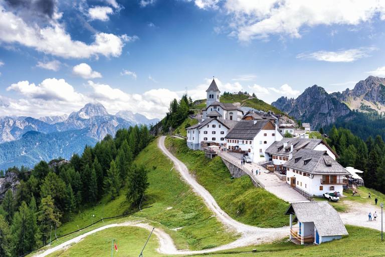 Village of monte Lussari with Julian alps in background. Tarvisio area, Udine province, Friuli Venezia Giulia region. Alpine village concept.