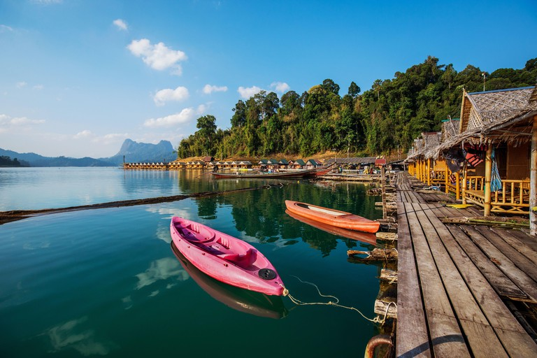 Wooden traditional thai longtail boat on Cheow Lan lake arriving to floating bungalow huts in Khao Sok National Park, Thailand