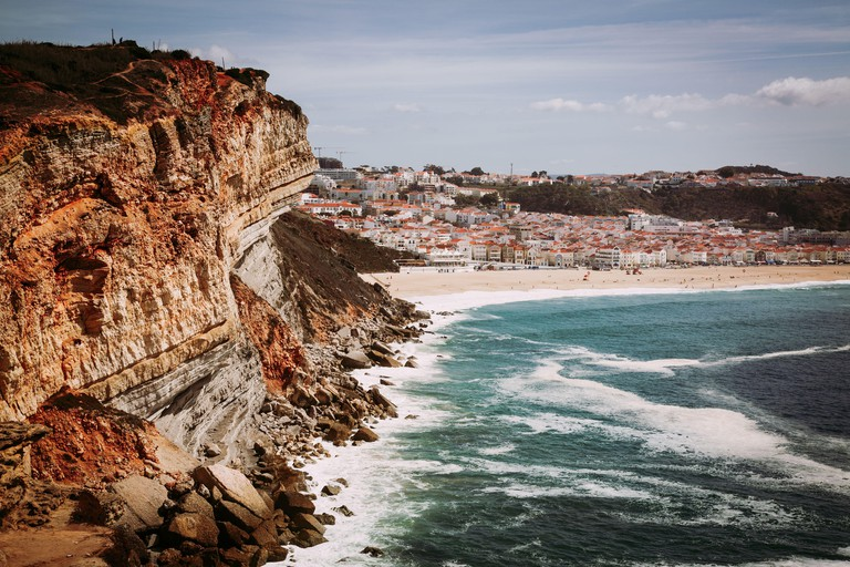 Nazare, Portugal: High Cliff over Atlantic Ocean with Nazare town in the background, Portugal