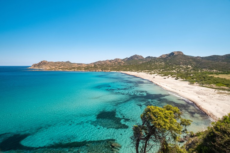 Translucent turquoise Mediterranean sea lapping onto an almost deserted Ostriconi beach in the Balagne region of Corsica with the Desert des Agriates