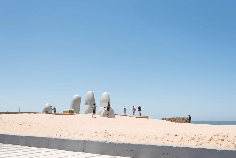 Punta del Este, Maldonado / Uruguay; Jan 1, 2019: The Hand, Fingers or Man Emerging to Life, a popular sculpture of five fingers emerging from the san