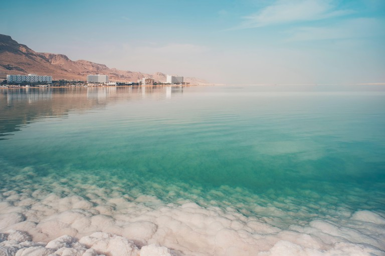 View of the coast and spa hotels at Dead Sea, Ein Bokek, Israel. Salt formations in the foreground. Travel Israel. large salt crystals.