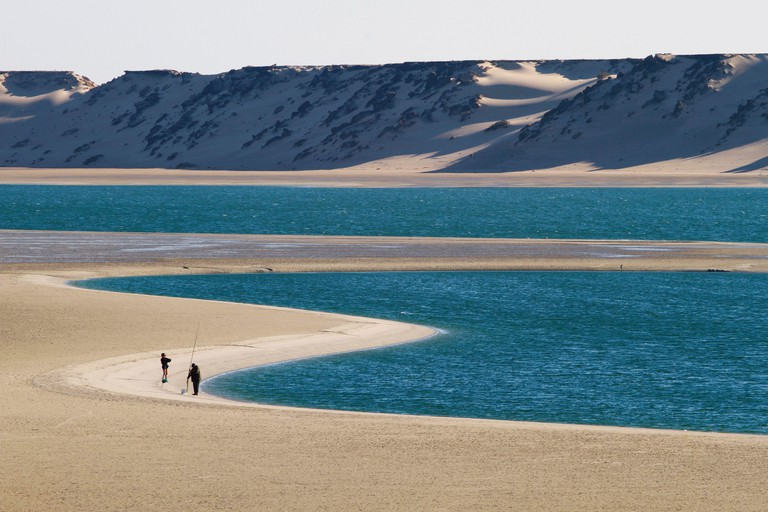 Morocco, Western Sahara, Dakhla, beach bordering the lagoon with the desert mountains in the background