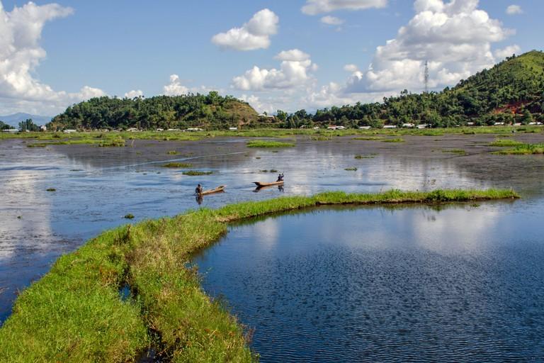 Two fishermen are sailing through the beautiful Loktak Lake manipur india.