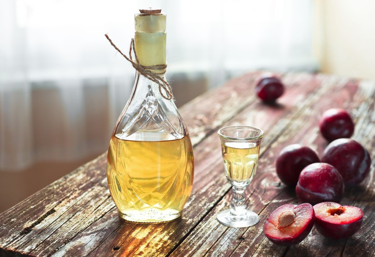 traditional Balkan plum brandy - rakija or rakia slivovica in the bottle, a wineglass with sljivovica and fresh plums