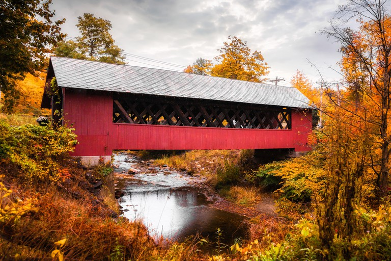 Beautiful Vermont covered bridge surrounded by colorful fall foliage.