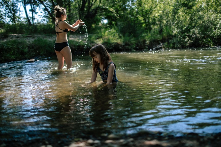 Two girls playing in a shallow creek on a summer day