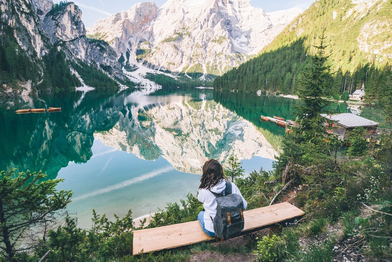 woman sitting on the bench looking at pragser wildsee in north italy. copy space. summer vacation