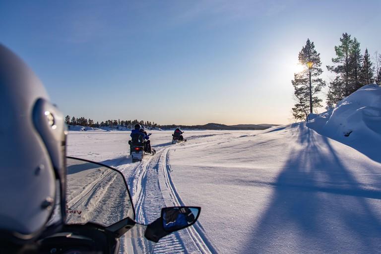 Snowmobile touristic tour on the frozen lake of Inari, in Lapland, Finland