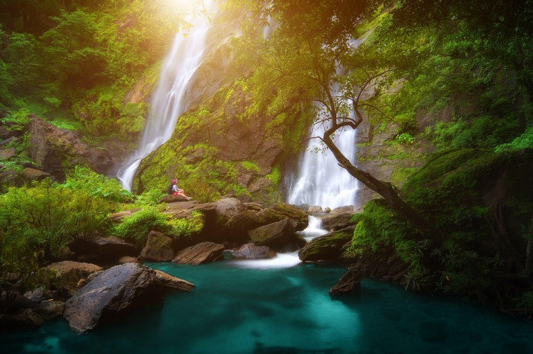 Backpacker sit in waterfall, Khlong Lan Waterfall was the last major waterfall Khlong Lan National Park, Kamphaeng Phet Thailand.