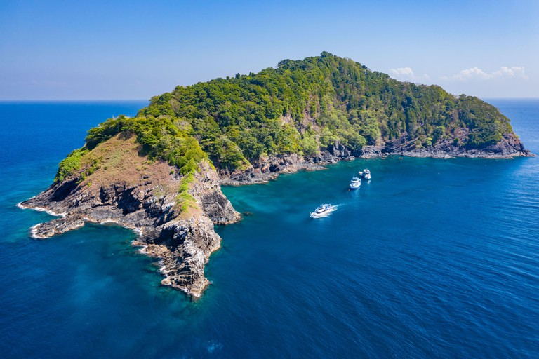 SCUBA diving boats and diver around a rugged, remote tropical island (Koh Bon island, Similan Islands, Thailand)..