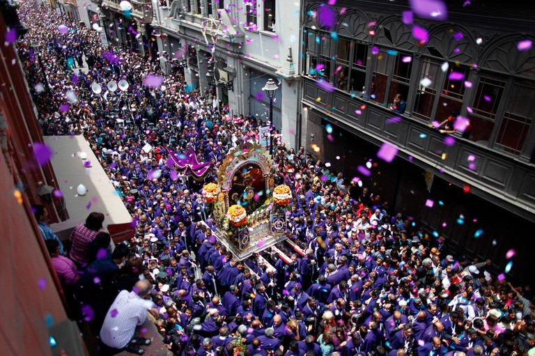 """Believers, dressed in purple, carry a replica of the painting of the """"Lord of Miracles"""", Peru's most revered Catholic religious icon, in a major procession through central Lima October 18, 2013. The painting can be traced back to the colonial era when an"""