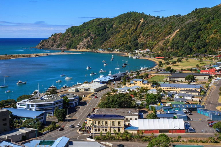 Panoramic view of the town of Whakatane, New Zealand, with many small boats on the harbor