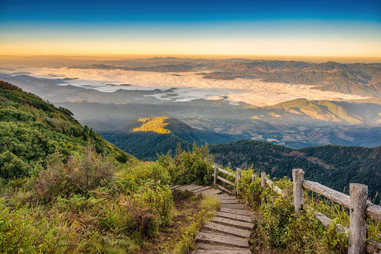 Tropical forest nature landscape view with toursits mountain range and moving cloud mist at Kew Mae Pan nature trail, Doi Inthanon, Chiang Mai Thailan