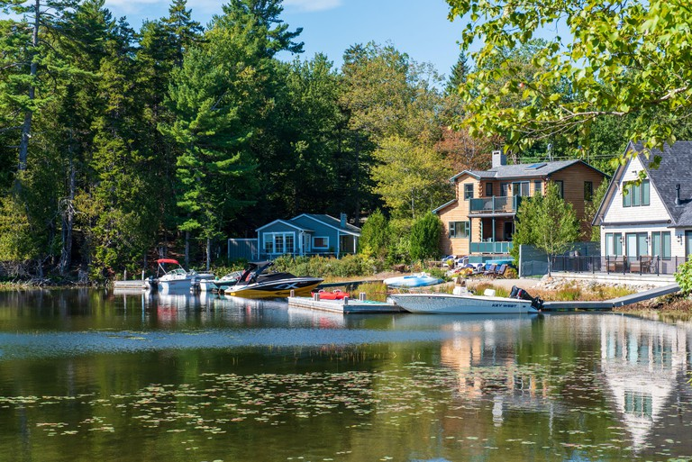 A colorful photo of waterfront houses in Bar Harbor Maine as the seasons begin to change in Autumn.