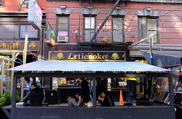 Customers enjoying pizza in the outdoor hut of Artichoke Basille's Pizza during Covid-19 pandemics.MacDougal Street.Greenwich Village.New York City.USA