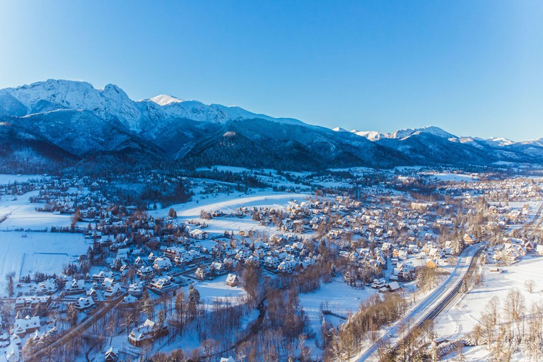 Aerial landscape of Zakopane, Poland during the winter season. Small houses and forest covered in snow with mountains in the background. High quality photo