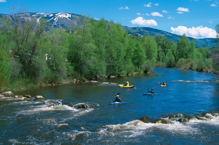 Kayakers in Yampa River Steamboat ski area Mt Werner Steamboat springs CO USA