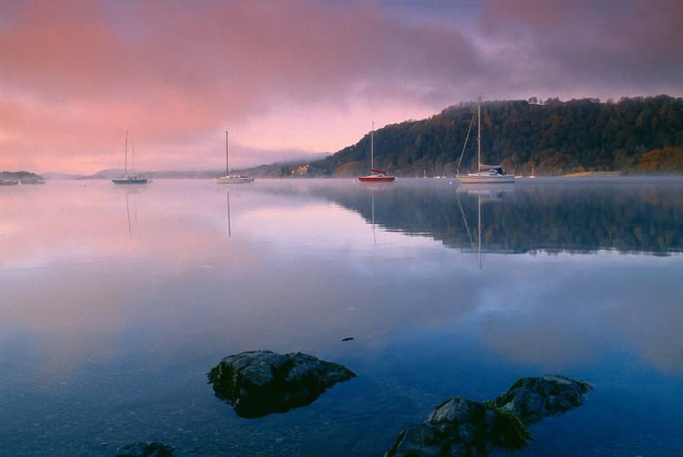 boats on Lake Windermere at dawn Lake District Cumbria England UK