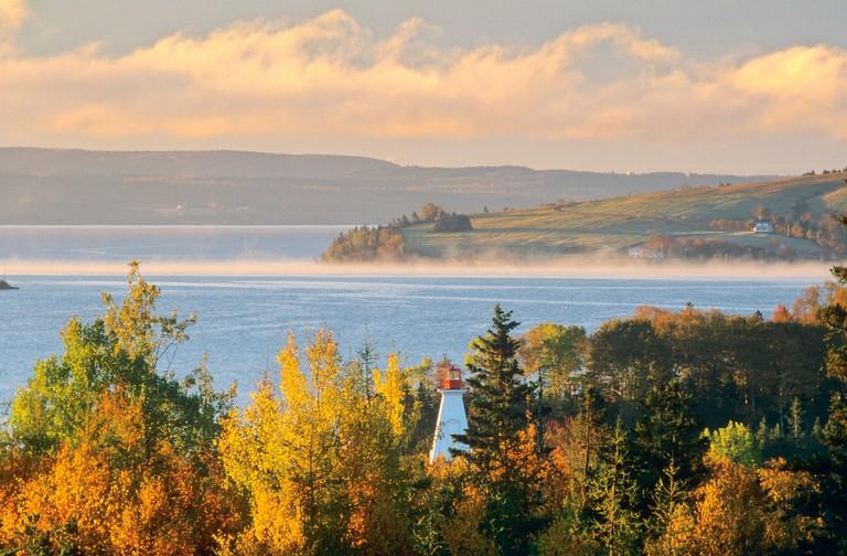 Early morning fog lifting off Bras d'Or Lake, Baddeck, Cape Breton, Nova Scotia, Canada.