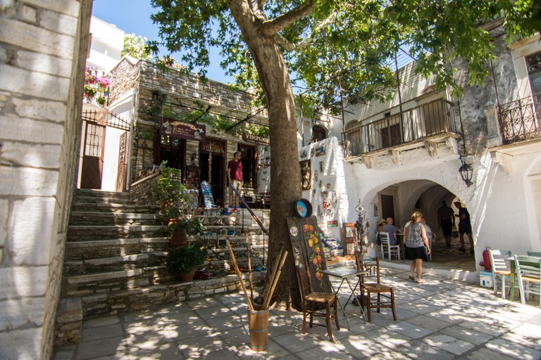 2AA9M5H Apiranthos, Naxos / Greece - July 13, 2019: Apeiranthos, Naxos / Greece - July 13, 2019: Toutists visiting the narrow streets and shops of Apiranthos, the Marble village in central Naxos, Greece
