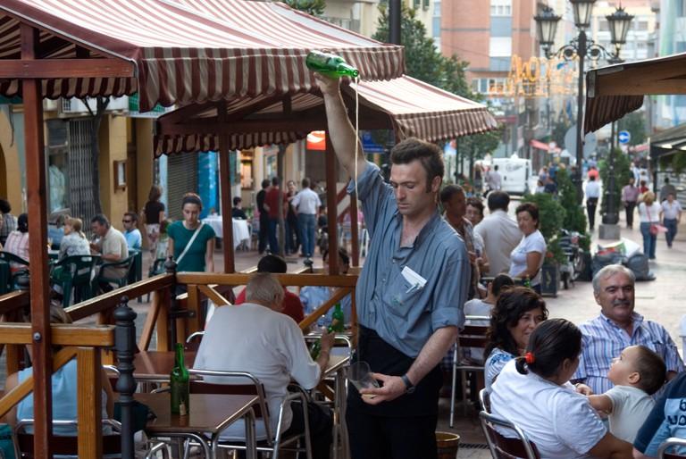 Barman pouring cider, Oviedo, Asturias, Spain