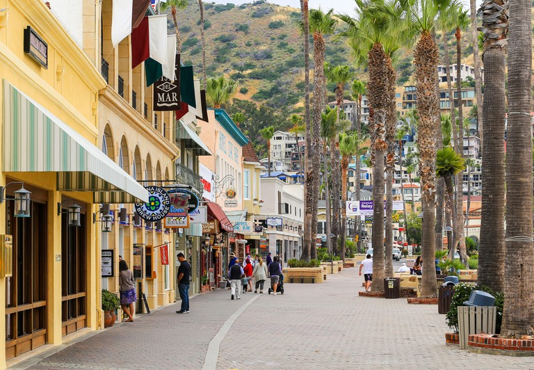 Avalon, California, USA - May 31, 2017: The boardwalk in Avalon (Santa Catalina Island) with shops on the left. People strolling around. W148DX