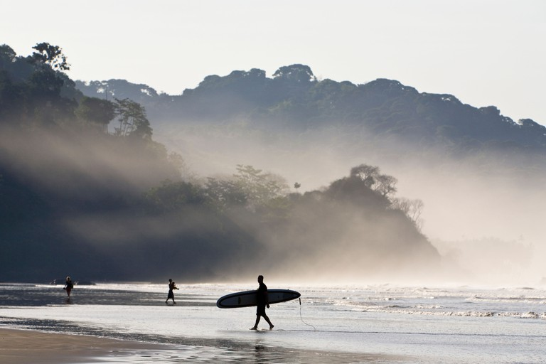 Surfers on the beach with sunlight shining through the morning mist at Playa Dominical in Puntarenas, Costa Rica.. Image shot 02/2009. Exact date unknown.