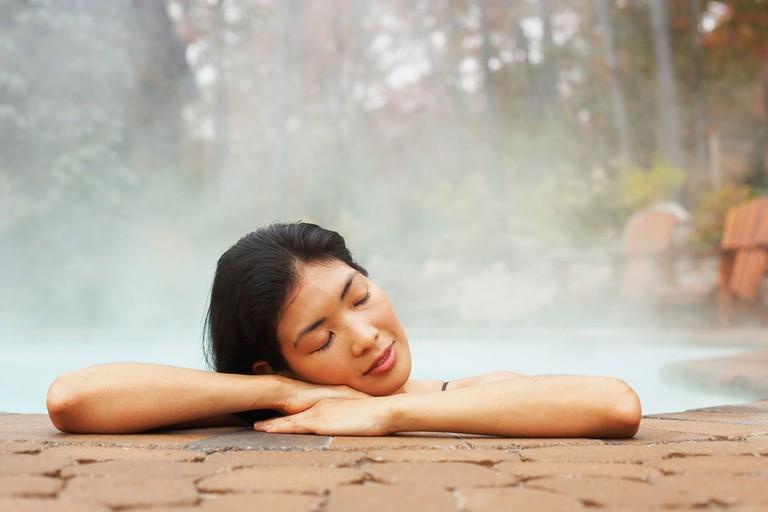 Asian woman sitting in hot tub