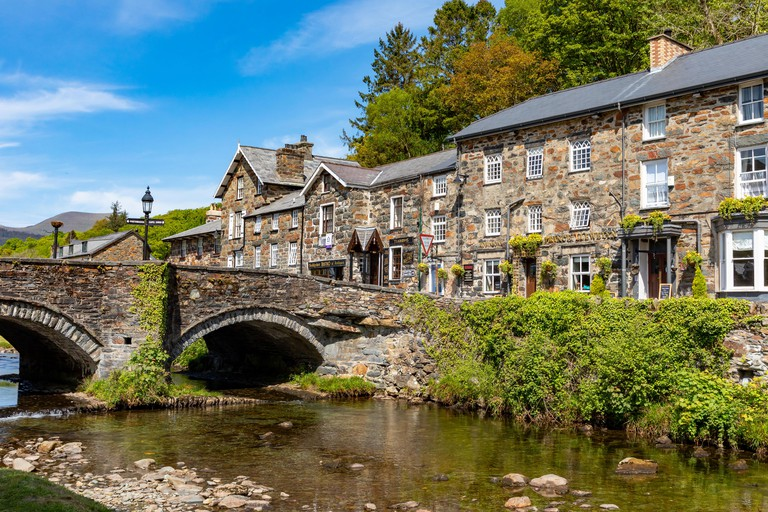 Attractive stone buildings beside the river Glaslyn, in Beddgelert, in the Snowdonia National Park_TA1XF1