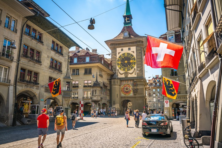 2CC9EP8 Bern Switzerland , 27 June 2020 : Old street view with tourists flags and Zytglogge clock tower in Kramgasse street in Bern old town Switzerland