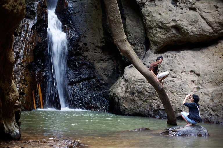 One tourist photographs another in front of Pam Bok waterfall near Pai in northern Thailand